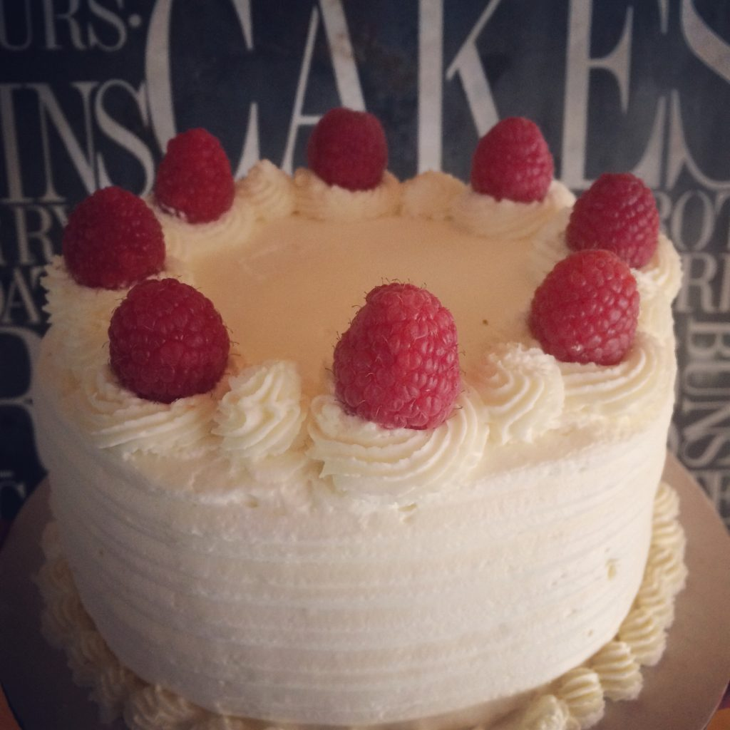 White cake made with wheat flower, raspberries on top of cake