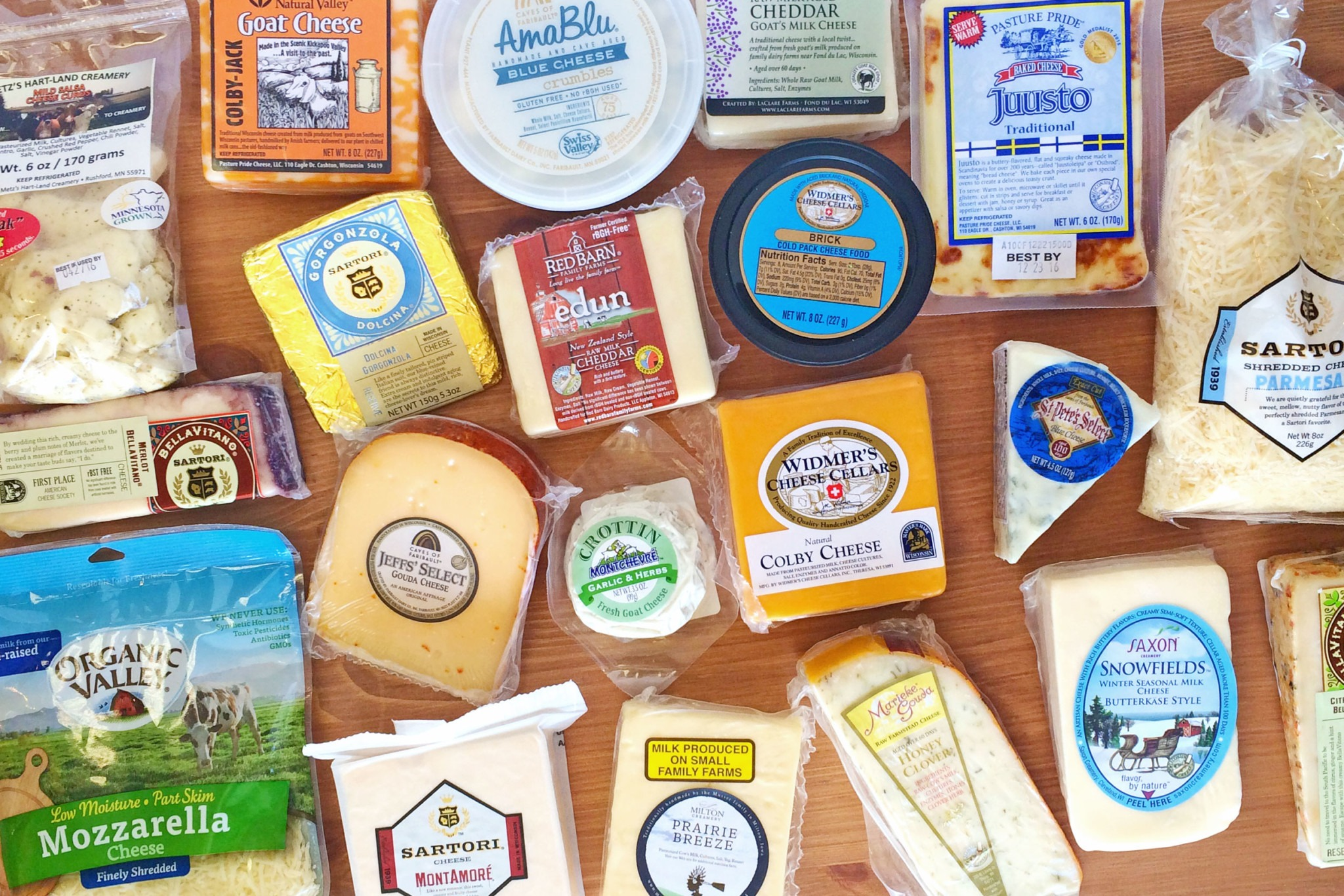 Large array of cheese products on a wooden table