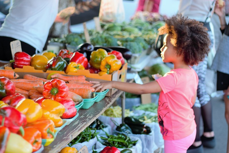 Little girl with fresh vegetables at Maple Grove Farmers Market