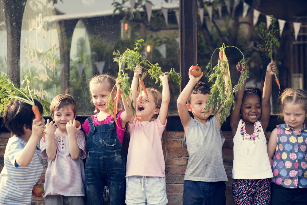 Young children holding fresh fruits and vegetables