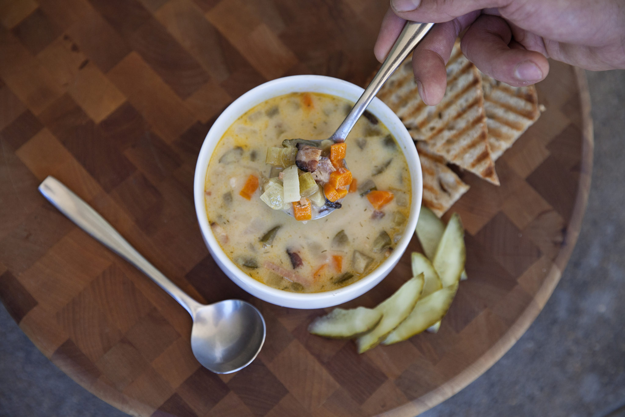 bowl of creamy soup with chunks of carrots and pickles with toasted bread on the side