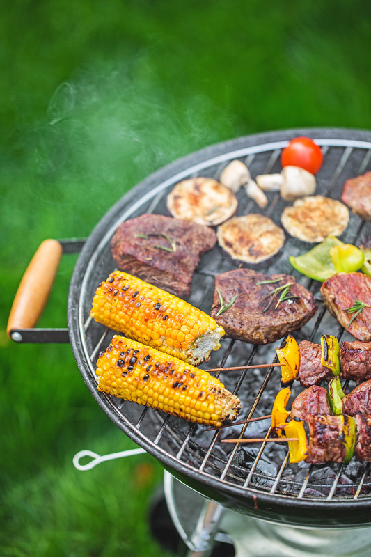 charcoal grill with corn, steaks, kabobs, mushrooms, peppers, and eggplant on it