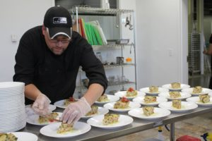 chef preparing food, bent over a table of plates with a focused expression
