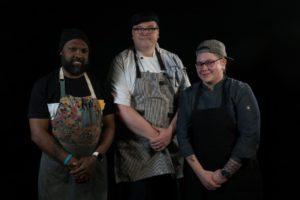 three chefs standing shoulder to shoulder in a dark room