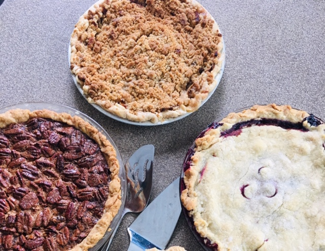 three fruite pies - apple crumble, pecan, and blueberry