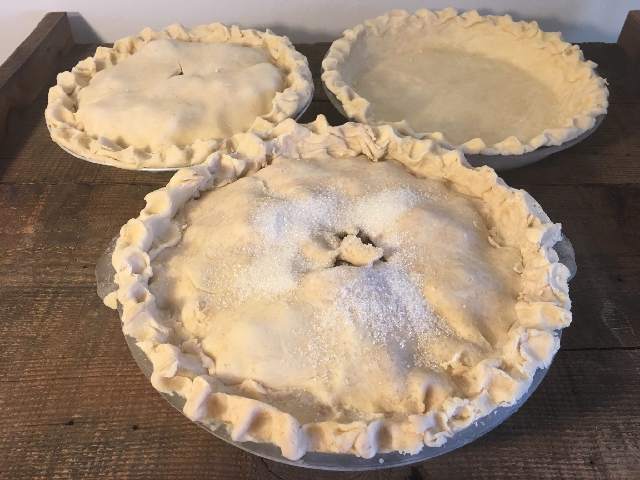 three uncooked pies with solid crusts