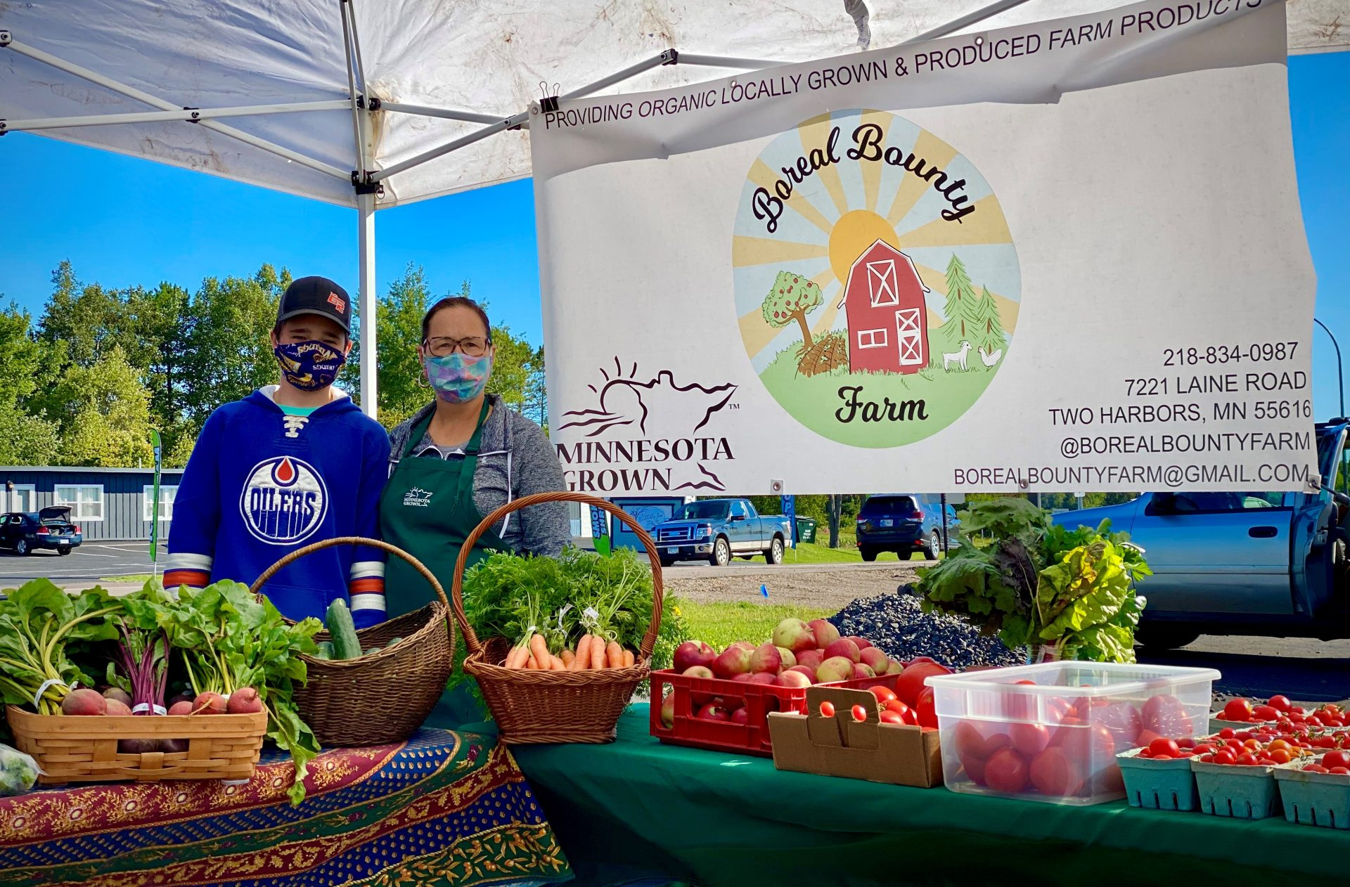 Member farm Boreal Bounty stands in front of farmers market banner purchased through cost share program.
