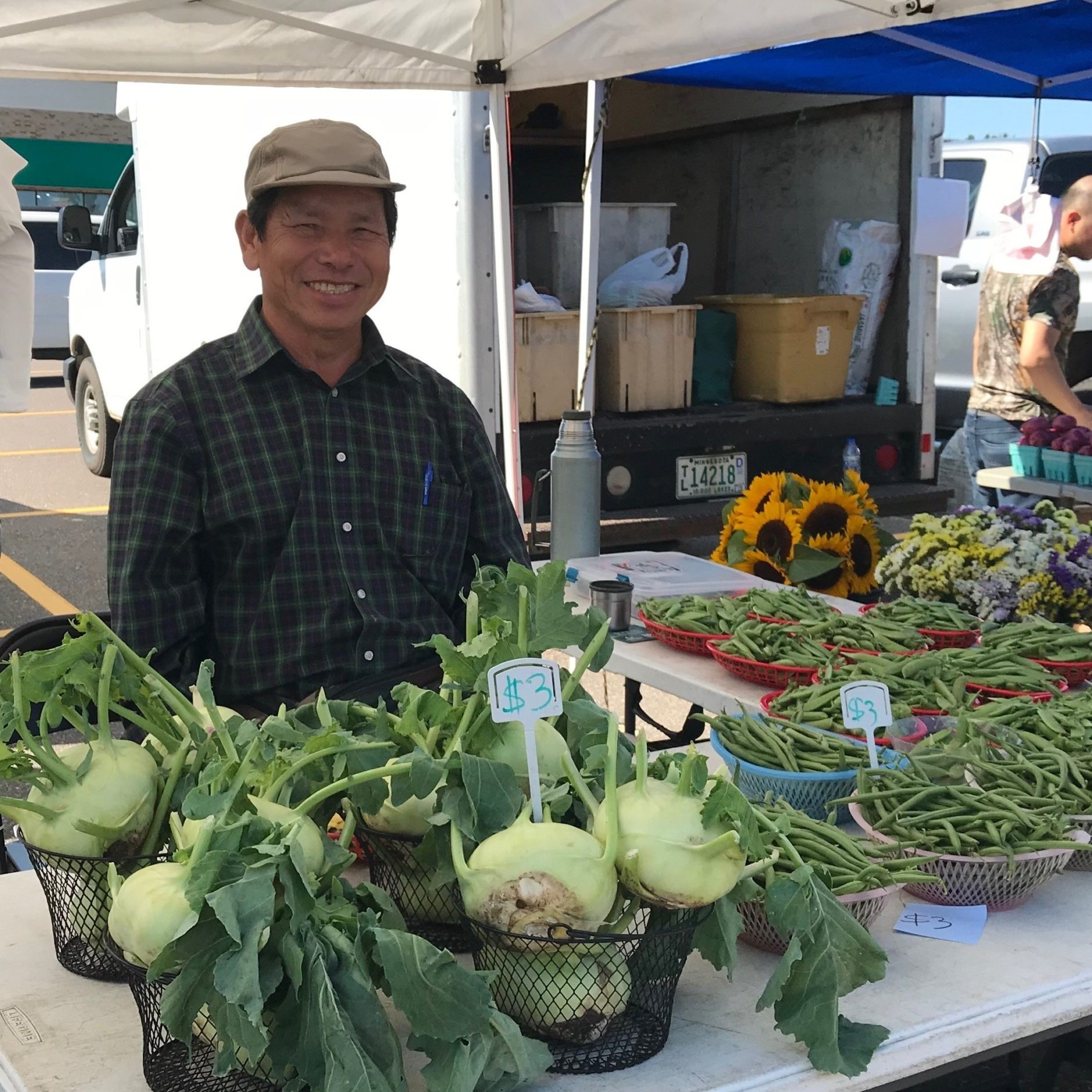man smiling behind booth selling kohlrabi and green beans