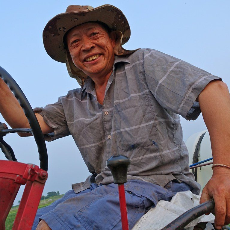 farmer smiling from a red tractor
