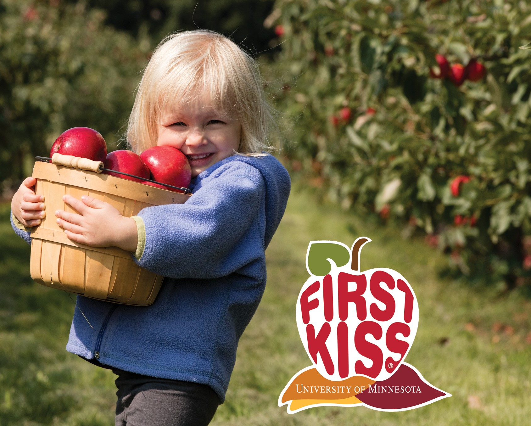 Little girl carrying a basket of apples with the logo First Kiss by University of Minnesota